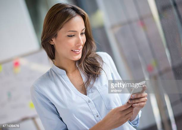 Asian business woman texting on her phone