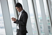Asian Businessman at window with phone