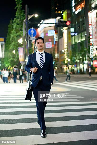 Asian businessman crossing street en Shibuya, Tokyo