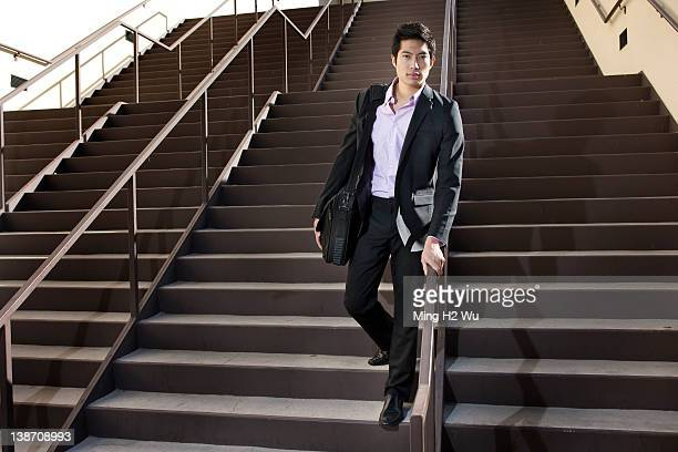 Asian businessman descending staircase