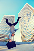 Asian businessman doing back flip on urban rooftop