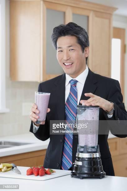 Asian businessman drinking fruit smoothie