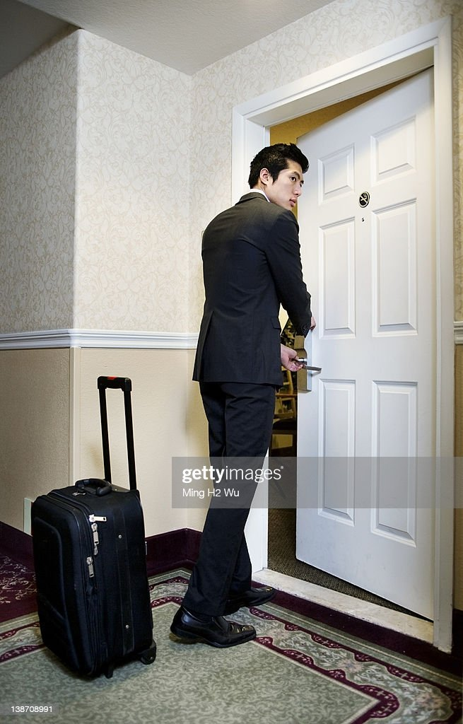 Asian businessman entering hotel room : Stock Photo