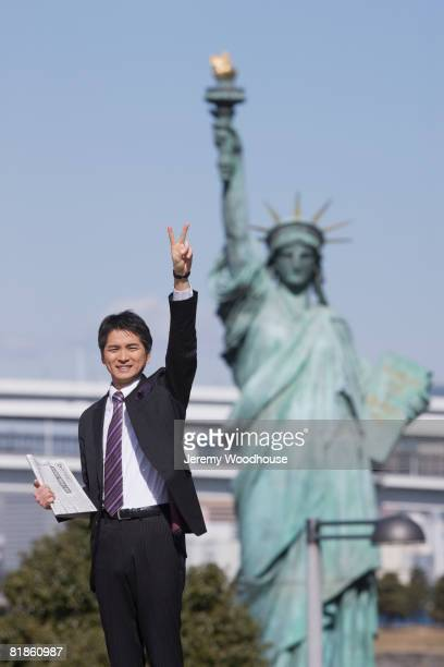 Asian businessman in front of Statue of Liberty replica