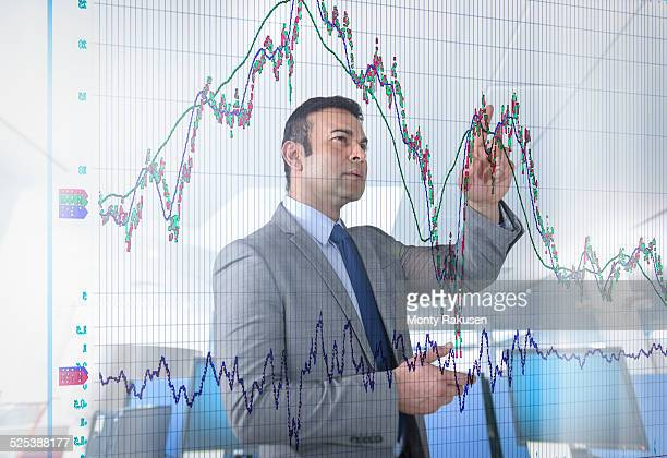 Asian businessman inspecting graph on interactive display