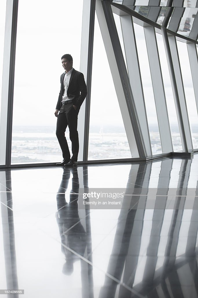 Asian Businessman looking out of window