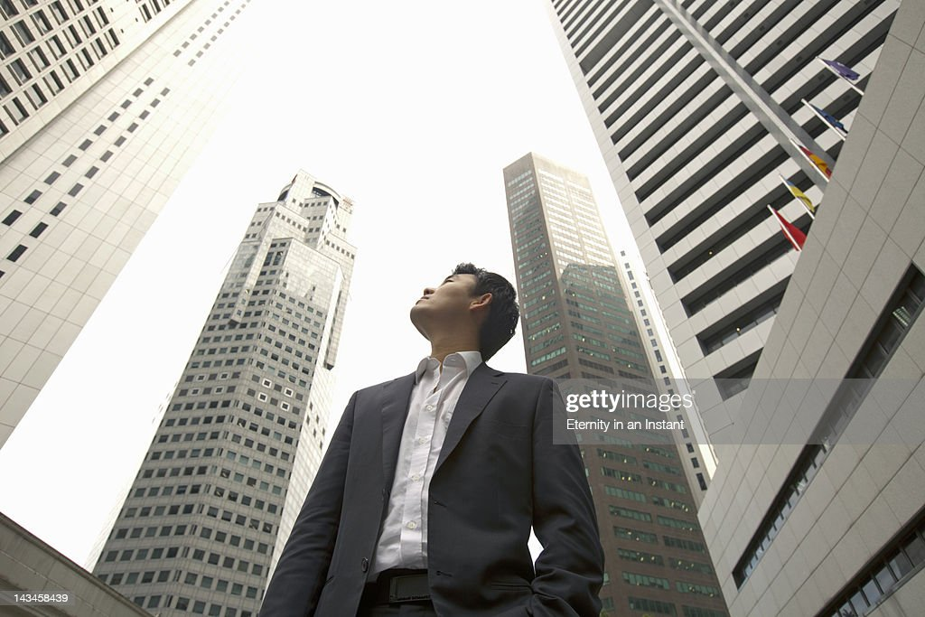Asian Businessman looking up at  buildings in city : ストックフォト