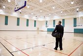 Asian businessman on empty basketball court