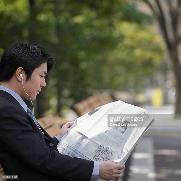 Asian businessman reading newspaper on park bench