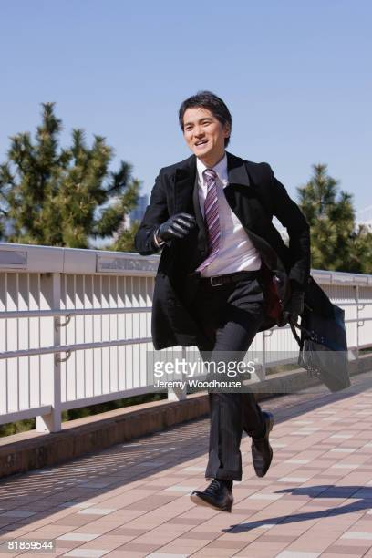 Asian businessman running with briefcase
