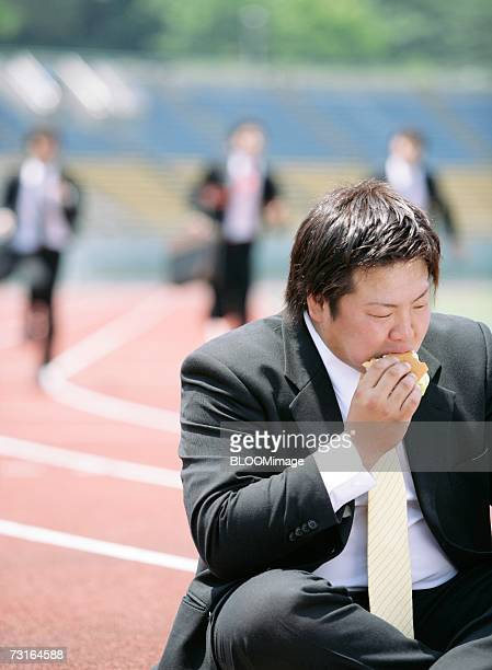 Asian businessman sitting and eating a food on field