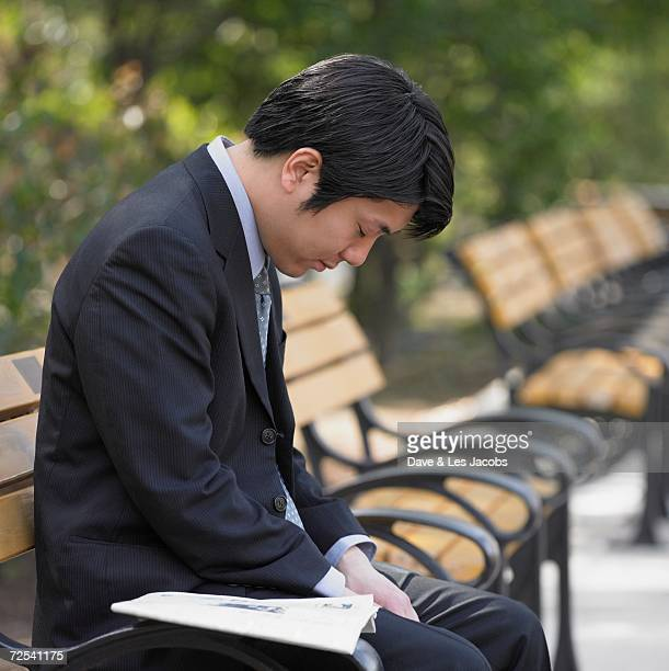 Asian businessman sitting and sleeping on park bench