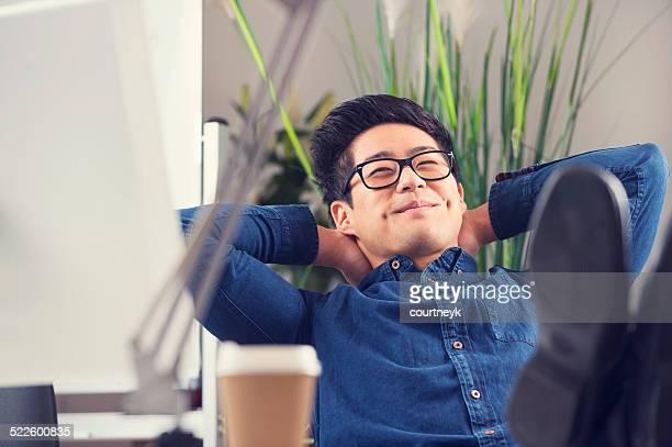 Uomo d'affari asiatico seduto alla sua scrivania di relax