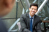Friendly smiling handsome Asian businessman sitting at office lounge talking with his colleague