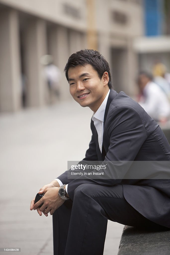 Asian Businessman, sitting, holding smartphone : Stock Photo
