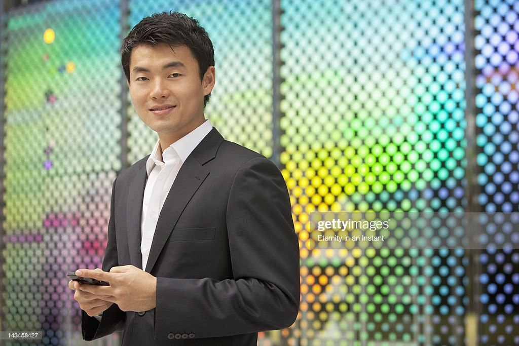 Asian Businessman smiling, holding smartphone : Stock Photo