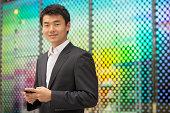 Asian Businessman smiling, holding smartphone