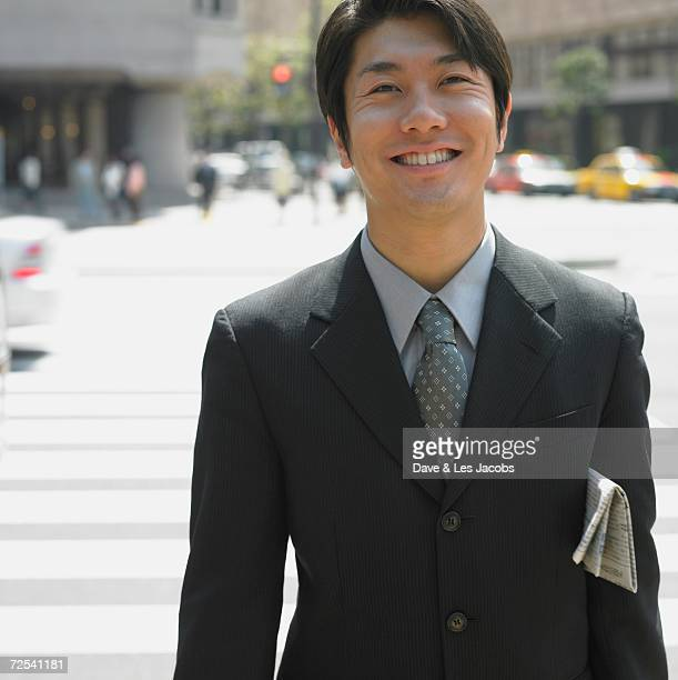 Asian businessman smiling in urban area