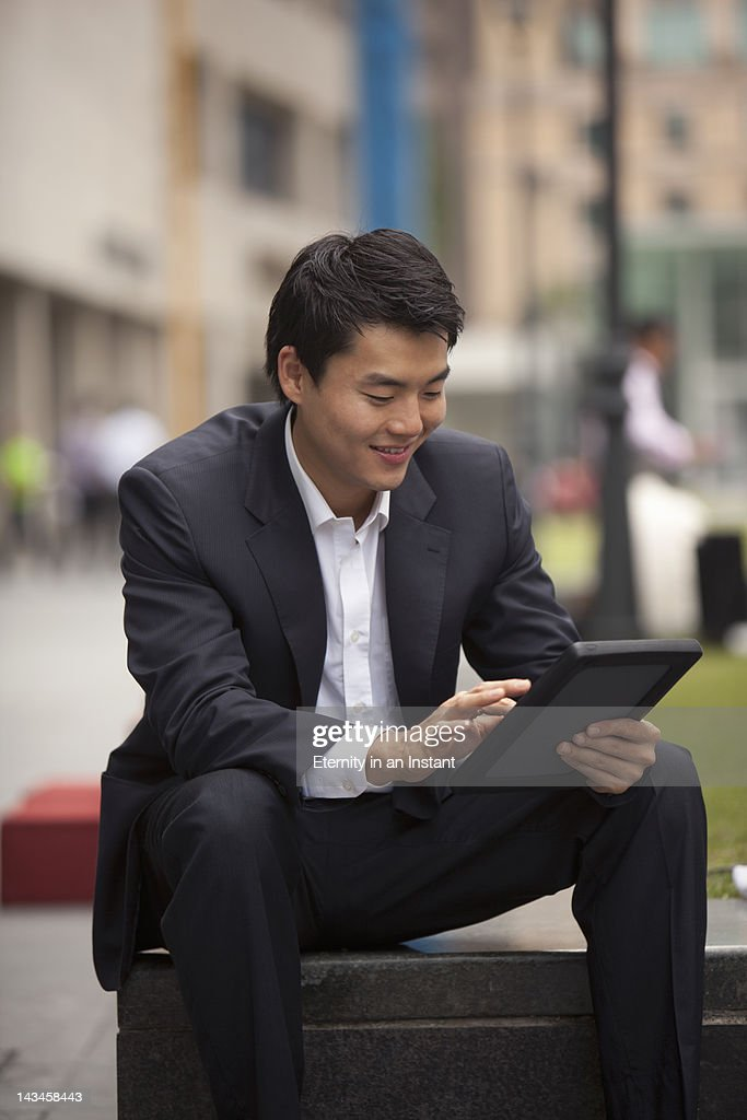 Asian Businessman smiling using digital tablet : Stock Photo