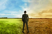 Asian businessman standing between different climate on the daylight