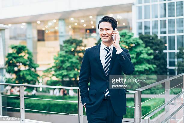 Asian businessman talking on smart phone outdoors