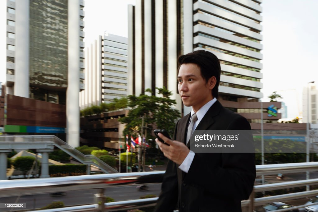 Asian businessman text messaging on cell phone outdoors : Stock Photo