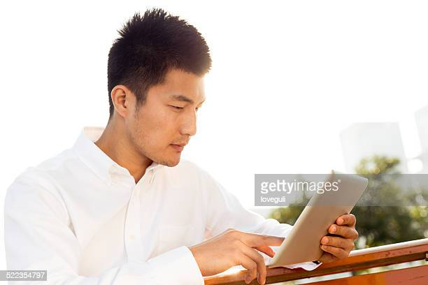 Asian businessman using app on tablet outdoor for financial report