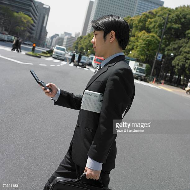 Asian businessman using cell phone in urban area