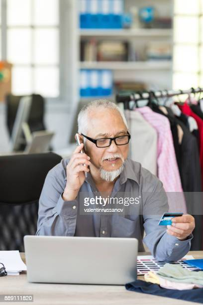 Asian businessman using credit card at workplace