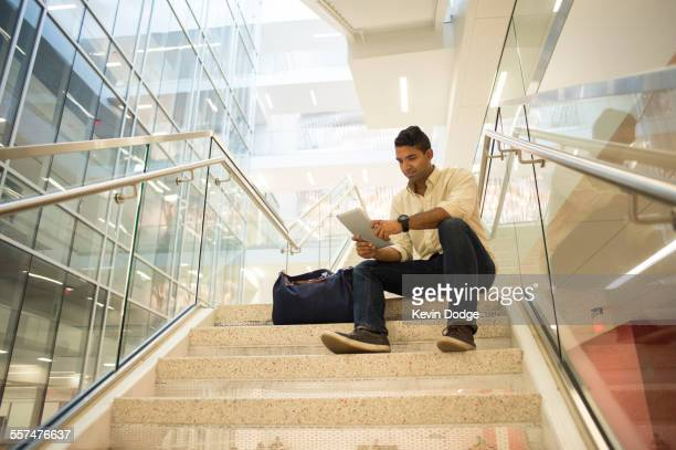 Asian businessman using digital tablet on office staircase