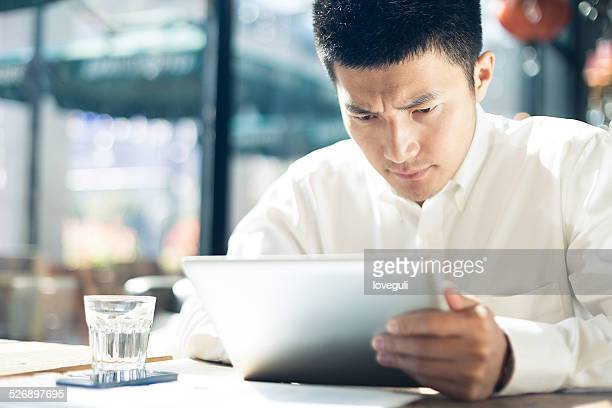Asian businessman using tablet during break in cafe.