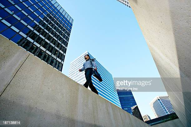 Asian businessman walking on ledge in city