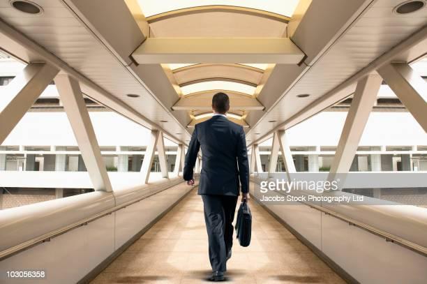 Asian businessman walking over skywalk