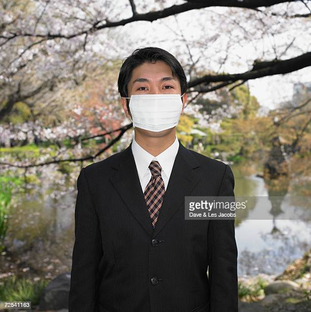 Asian businessman wearing surgical mask in park