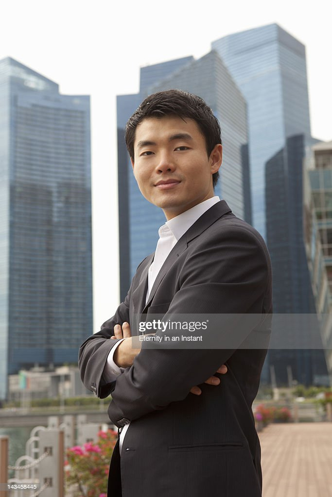 Asian businessman with city behind : Stock Photo