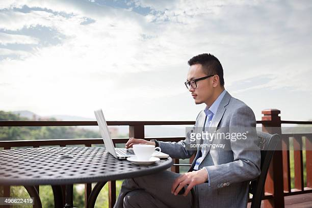 Asian businessman working in the outdoor Coffee Hall
