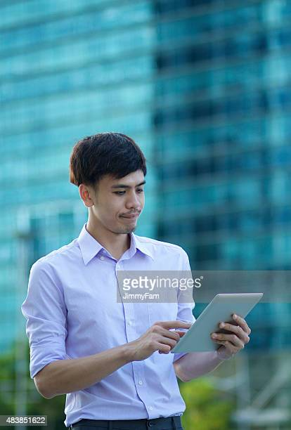 Asian businessman working outdoors with a tablet