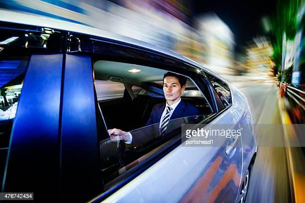 Hommes d'affaires asiatiques à l'arrière de siège de voiture