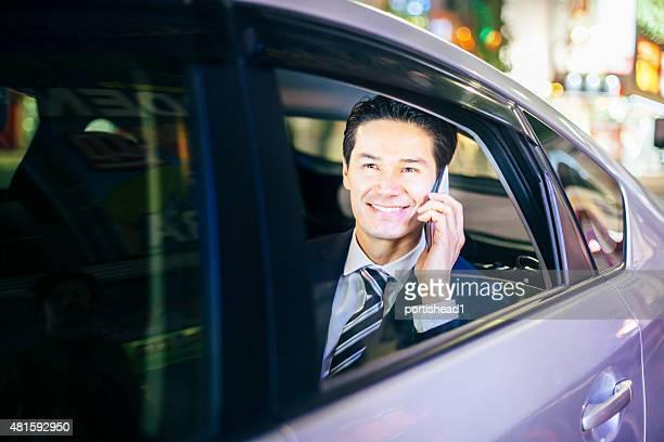 Asian businessmen at back seat of car