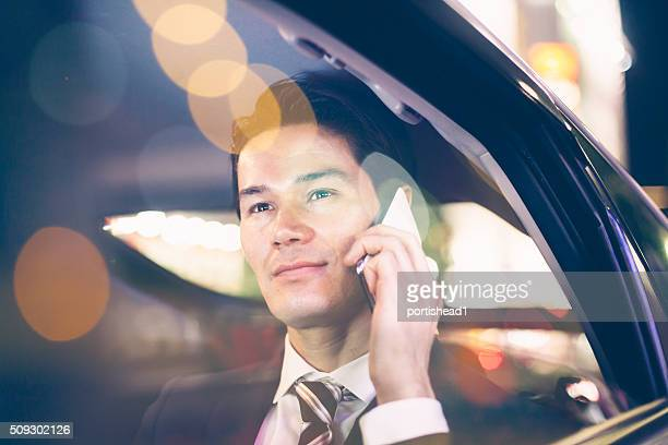 Asian businessmen at back seat of car