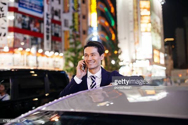 Asian businessmen standing next to his car