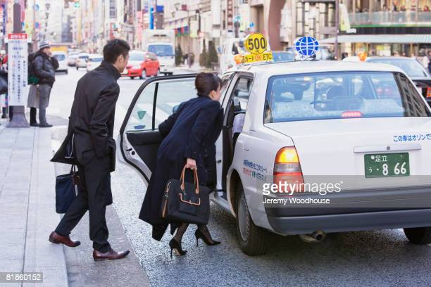 Asian businesspeople getting into taxi cab
