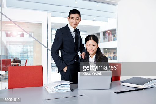 Asian businesspeople looking in camera with laptop : Stock Photo