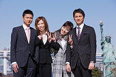 Asian businesspeople standing arm in arm