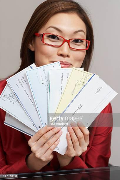 Asian businesswoman holding checks