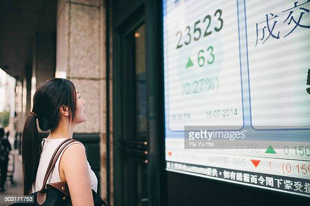 Asian businesswoman looking at stock quote board