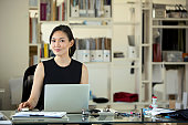 Asian Businesswoman on laptop computer in office