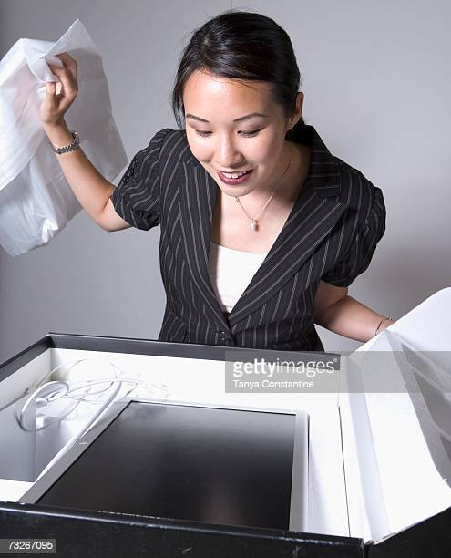 Asian businesswoman opening box with new computer