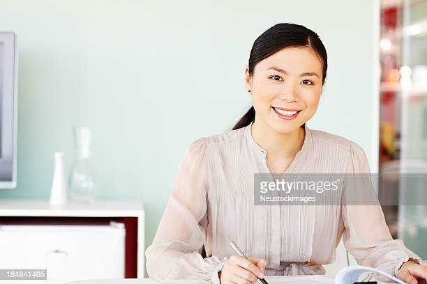 Asian Businesswoman Sitting at Her Desk