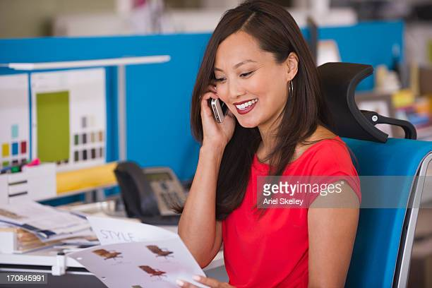 Asian businesswoman talking on cell phone at desk